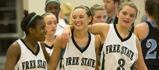Free State seniors A&#39;Liyah Rogers (4), Kennedy Kirkpatrick (11) and Abbey Casady (3) walk off the court following Free State&#39;s overtime victory against Shawnee Mission East, Tuesday, Feb. 19, 2013 at Free State.