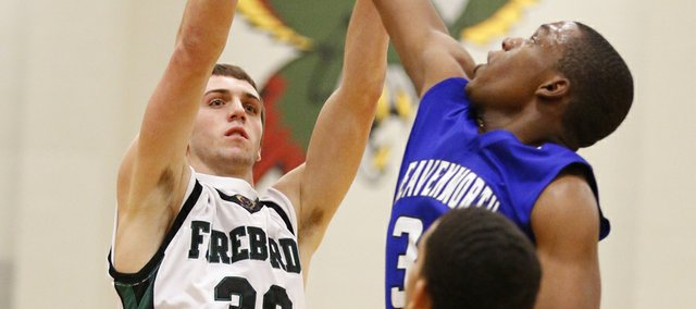 Free State forward Kyle McFarland puts up a shot against Leavenworth defenders Grant Lang, back, and Jeff George (11) during the second half on Tuesday, Feb. 5, 2013 at Free State High School.