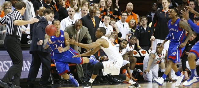 Kansas guard Travis Releford dives to push the ball ahead of Oklahoma State guard Markel Brown to run out the clock against Oklahoma State in double overtime on Wednesday, Feb. 20, 2013 at Gallagher-Iba Arena in Stillwater, Oklahoma.