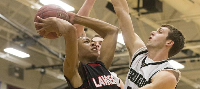 Lawrence High's John Barbee, left, hangs in the air as he tries to shoot over Free State's Kyle McFarland, right, during their game Friday night at Free State.