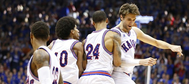 Kansas center Jeff Withey, right, bumps teammates Travis Releford (24) and Kevin Young after a bucket against Texas Christian during the second half on Saturday, Feb. 23, 2013 at Allen Fieldhouse.