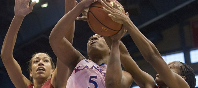 "Kansas sophomore forward Bunny Williams (5) powers the ball up through a double team of Nicole Griffin (4) and Sharane Campbell (24) during Kansas' annual ""Jayhawks for a Cure"" cancer awareness game against Oklahoma, Sunday, Feb. 17, 2013 at Allen Fieldhouse."