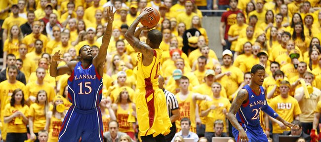 Kansas guard Elijah Johnson extends to defend against a three from Iowa State guard Korie Lucious during the first half on Monday, Feb. 25, 2013 at Hilton Coliseum in Ames, Iowa.