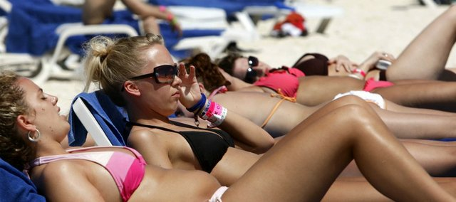 A group of spring breakers from Alberta, Canada, soak up the sun in Cancun, Mexico, in this March 14, 2006, file photo. Many students are preparing for spring break, but tanning, binge drinking and crash diets aren't the way to go. Lawrence experts offered healthier alternatives.