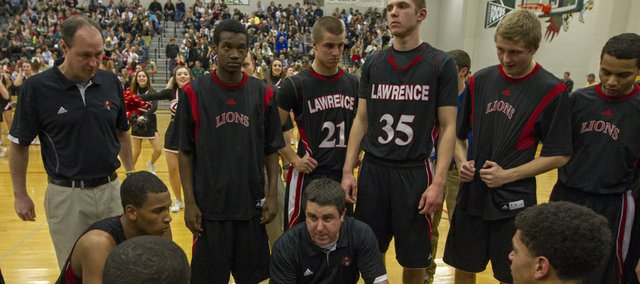 Lawrence High coach Mike Lewis talks to his team late in the fourth quarter during their game against Free State Friday night at Free State.