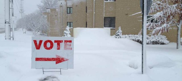 A sign pokes out from the snow to direct Lawrence voters to the Presbyterian Manor polling place Tuesday morning.