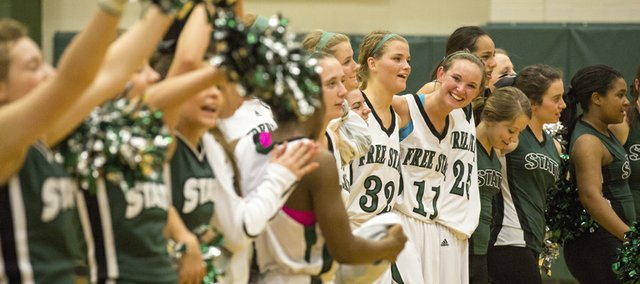 Free State senior Kennedy Kirkpatrick (11) smiles as she joins in with her teammates and the Firebird cheerleaders while they sing the alma mater following Free State's first round 6A sub-state game against Olathe North Thursday evening at FSHS. The Firebirds advanced with a 57-44 win.