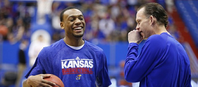 Kansas guard Naadir Tharpe laughs with assistant Joe Dooley prior to tipoff against West Virginia on Saturday, March 2, 2013 at Allen Fieldhouse.