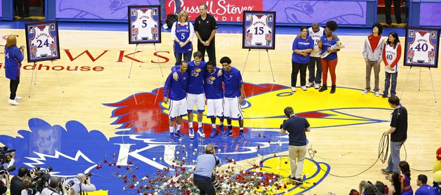 Kansas seniors Travis Releford, left, Jeff Withey, Elijah Johnson and Kevin Young huddle at midcourt for a photo as they are presented before the Allen Fieldhouse crowd with their families on senior night prior to tipoff against Texas Tech, Monday, March 4, 2013.