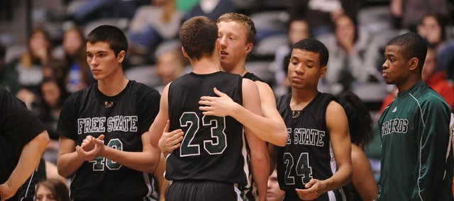 Free State's Weston Hack (21) consoles teammate Cody Scott (23) after the Firebirds' 56-37 loss in the first round of the Class 6A state tournament on Wednesday, March 6, 2013, in Wichita.