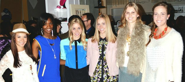 Fashion bloggers Emily Kennedy, third from left, and her sister Elizabeth Kennedy, third from right, pose with models in outfits the bloggers styled for the Kansas City Fashion Week kick-off party fashion show at Garment District Boutique in Kansas City's Power and Light District.