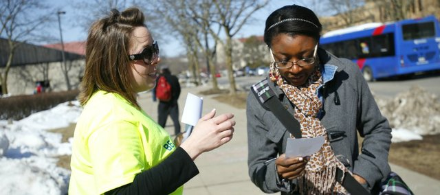 Lawrence resident Erin Harmon, left, passes out a flier promoting registration for a bone marrow drive to Kansas University senior Andi Darden, of Lansing, on Wednesday on the KU campus. The drive is organized through Be The Match by friends and family members of recent KU graduate Laura Hollar, Overland Park, who has acute lymphoblastic leukemia. The registration drive will take place between 10 a.m. and 3 p.m. Monday, March 11, 2013, at KU Credit Union, 3400 W. Sixth St.