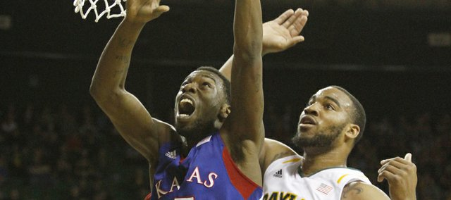 Kansas guard Elijah Johnson (15) lays in a basket past Rico Gathers (2) in KU's game against the Baylor Bears on Saturday in Waco, Texas.