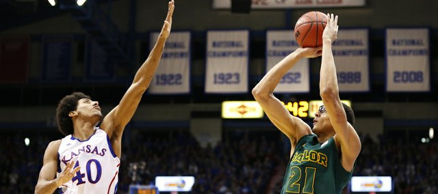Kansas forward Kevin Young comes in to defend against a three-point shot from Baylor center Isaiah Austin during the second half on Monday, Jan. 14, 2013 at Allen Fieldhouse.