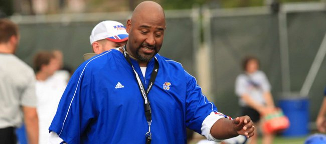 Kansas University defensive-line coach Buddy Wyatt oversees warm-ups in this photo from practice on Aug. 3, 2012.