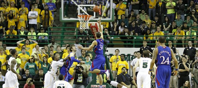 Perry Ellis (34) splits defenders for a layup in KU's 81-58 loss to the Baylor Bears Saturday in Waco.