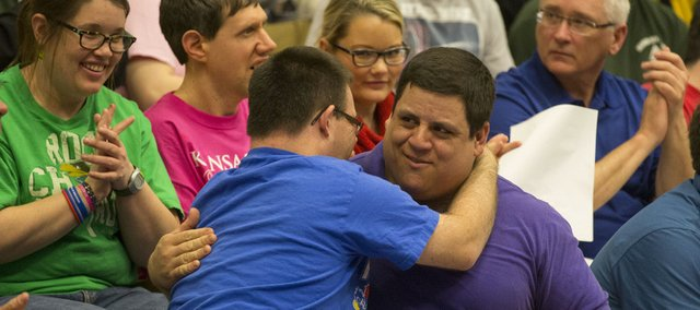 Brady Tanner receives a hug from Special Olympics teammate Ryan Banning Thursday night honoring Brady's induction into the American Indian Athletic Hall of Fame. His family and friends gathered for a ceremony at the Coffin Complex on the campus of Haskell Indian Nations University.