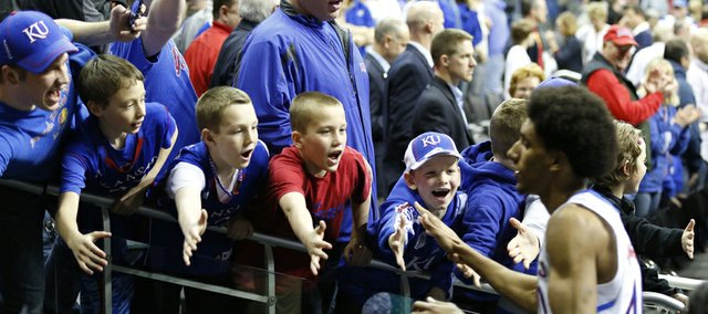 A row of young Kansas fans stretch themselves to slap hands with the Jayhawks as they leave the court following their 91-63 win over Texas Tech on Thursday, March 14, 2013 at the Sprint Center in Kansas City, Missouri.