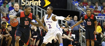 Kansas guard Rio Adams defends against Texas Tech guard Daylen Robinson during the second half of the second round of the Big 12 tournament on Thursday, March 14, 2013 at the Sprint Center in Kansas City, Missouri.