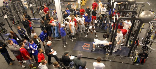 As NFL scouts look on, Jayhawks gather to encourage a participant in the bench-press portion of the Kansas University football pro timing day on Friday, March 15, 2013.