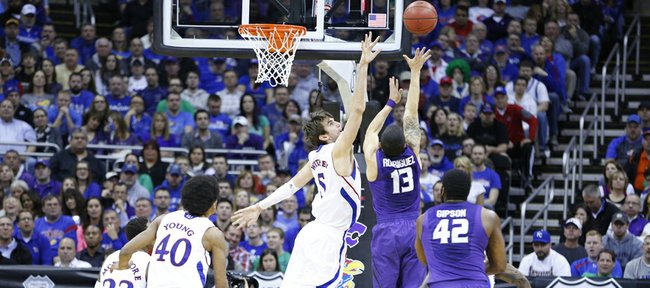 Kansas center Jeff Withey defends against a shot from Kansas State guard Angel Rodriguez during the second half of the Big 12 tournament championship on Saturday, March 16 2013 at the Sprint Center in Kansas City, Mo.