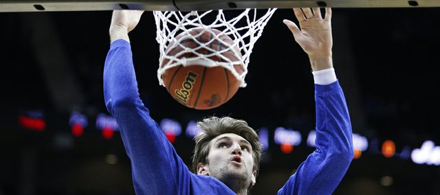 Kansas center Jeff Withey dunks during warmups prior to tipoff against Kansas State in the Big 12 tournament championship on Saturday, March 16, 2013 at the Sprint Center in Kansas City, Mo.