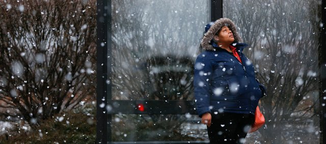 Lawrence resident Renee Clark watches as the snow comes down while waiting for a bus on Tuesday, March 19, 2013 at a stop in North Lawrence. Nick Krug/Journal-World Photo