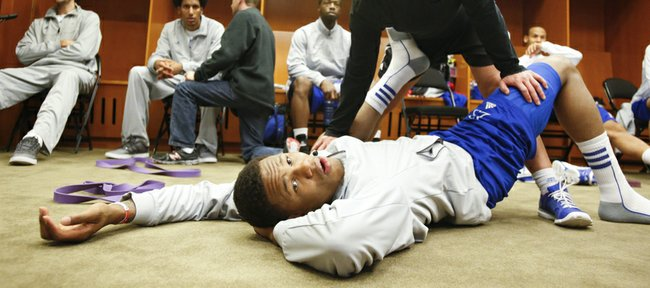 Kansas guard Ben McLemore and Andrea Hudy, assistant athletic director for sport performance watch the Colorado State and Louisville game as McLemore is stretched in the locker room before the team's practice, Saturday, March 23, 2013 at the Sprint Center in Kansas City, Mo.