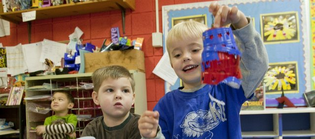 Andrew Neuenswander, left, and Brody Hermann, right, preschoolers at the First Presbyterian Church preschool, 2145 Clinton Parkway, combine plastic cup pieces that they will melt to create artistic sculptures.