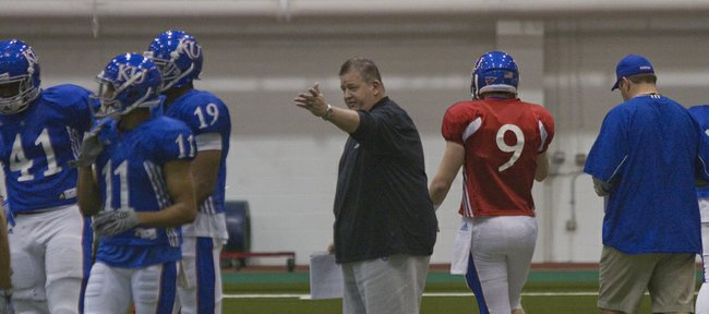 Kansas University football coach Charlie Weis, center, directs tight end Jimmay Mundine (41), receivers Tre' Parmalee (11) and Justin McCay (19) and quarterback Jake Heaps (9) during spring drills on March 9, 2013, at Anschutz Sports Pavilion.