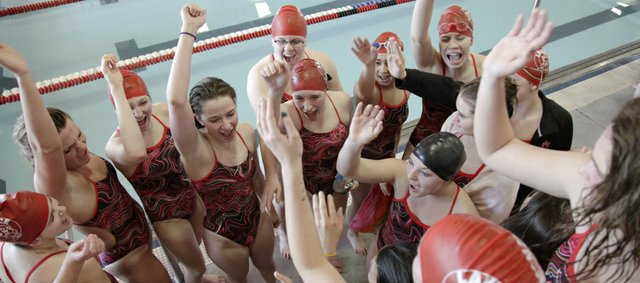 Lawrence High 200 medley relay team members cheer their teammate, junior Annie Odrowski, during the final leg of the race on Tuesday, March 26, 2013, in the Lawrence Invitational at LHS. Swimmers, from left, are junior Gretchen Frick, senior Heather Cistola, and senior Miranda Rohn. The Lions placed first in the event.