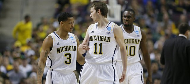 Michigan guard Nik Stauskas (11) talks with guards Trey Burke (3) and Tim Hardaway Jr. (10) in the first half of a third-round game of the NCAA college basketball tournament against Virginia Commonwealth Saturday, March 23, 2013, in Auburn Hills, Mich.