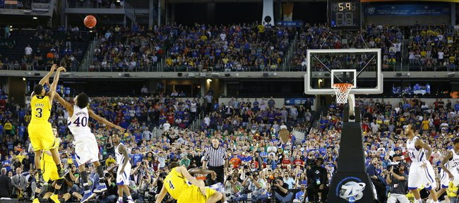 Kansas forward Kevin Young watches a three from Michigan guard Trey Burke go up with 5.9 seconds left in regulation on Friday, March 29, 2013 at Cowboys Stadium in Arlington, Texas.