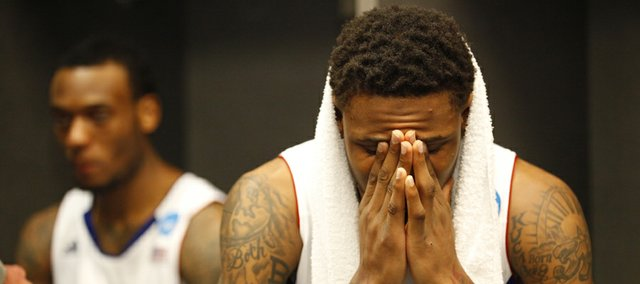 Kansas guard Ben McLemore puts his head in his hands as teammate Naadir Tharpe, background, answers a question from media members in the locker room after the Jayhawks' 87-85 overtime loss to Michigan on Friday, March 29, 2013 at Cowboys Stadium in Arlington, Texas.