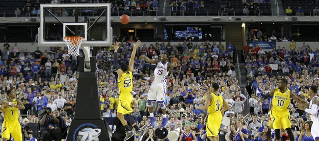 With only a few second on the clock and down by two points Elijah Johnson passes out to Naadir Tharpe for a last three-point attempt that missed leaving the Jayhawks with a 87-85 loss to the University of Michigan, Friday, March 29, 2013, at Cowboys Stadium, in Arlington, TX.