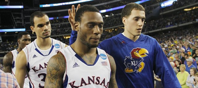 Kansas guard Christian Guard Naadire Tharpe (1) walks off the court with Perry Ellis, left, and Christian Garrett, right after the  Jayhawks 87-85 loss to the University of Michigan, Friday, March 29, 2013, at Cowboys Stadium, in Arlington, TX.