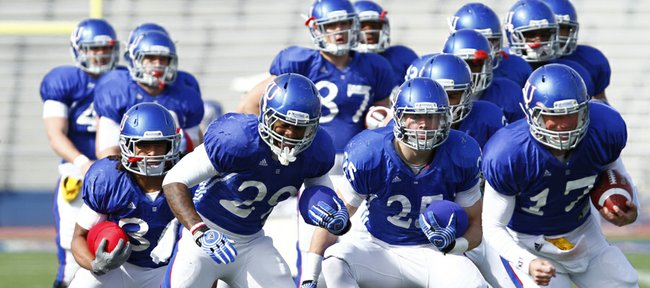 Kansas University running backs and quarterbacks shuffle through a drill during a spring football practice on Tuesday, April 2, 2013, at Memorial Stadium. From left, in front, are running backs Taylor Cox, James Sims, Brandon Bourbon and quarterback Blake Jablonski.