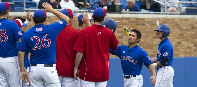 Kansas' Justin Protacio is greeted by teammates after scoring a run during Kansas' game against Oklahoma State Sunday afternoon at Hoglund Ballpark.