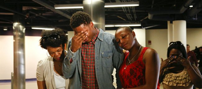 Kansas guard Ben McLemore wipes away tears as he leaves a news conference with family members after declaring his intention to enter the 2013 NBA Draft. At left is his mother, Sonja Reid Nick Krug/Journal-World Photo