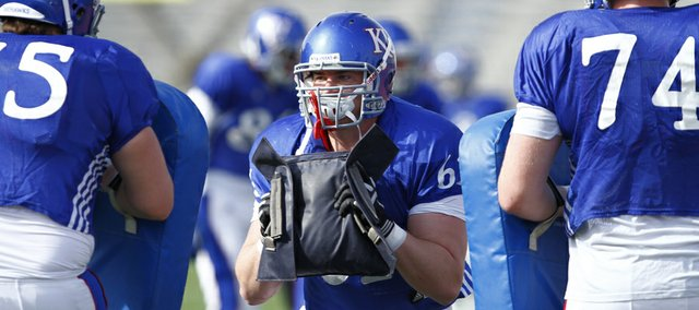 Kansas offensive lineman Pat Lewandowski (61) works through a drill with the other linemen during a spring practice on Tuesday, April 2, 2013 at Memorial Stadium.