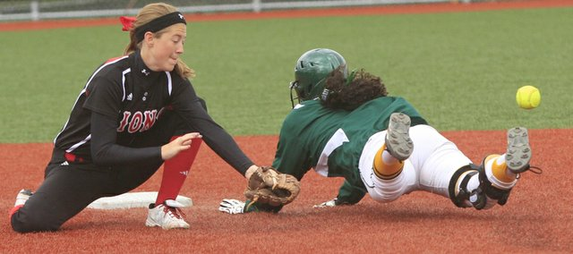Lawrence High shortstop Morgan Byrn, left, misses the tag on Shawnee Mission South's Justice Scales during a softball doubleheader on Thursday, April 11, 2013, at LHS. The Lions won the first game, 9-2, but lost the second, 8-1.