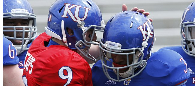 Kansas quarterback Jake Heaps gives KU running back/receiver Tony Pierson a pat on his helmet after Pierson scored the first touchdown on Saturday, April 13, 2013 during the KU football spring g