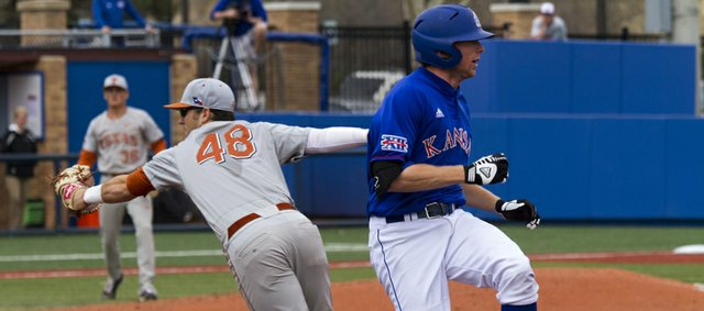 Kansas' Kevin Kuntz beats out a throw to first base as Texas' Ty Marlow is unable to handle the throw during Kansas' game against Texas Sunday afternoon at Hoglund Ballpark.