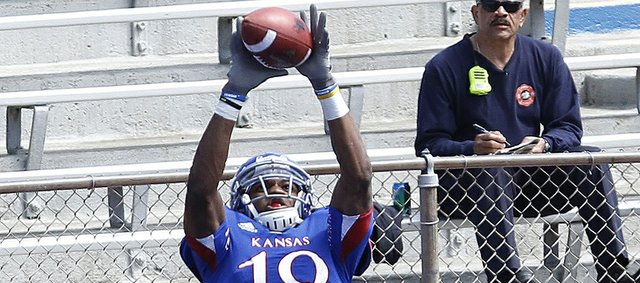 Kansas receiver Justin McCay stretches out to grab a pass for a touchdown against the White team's Deron Dangerfield on Saturday, April 13, 2013, at the KU football spring game. The Blue team won, 34-7.