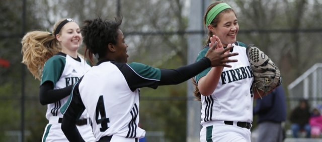 Free State shortstop A'Liyah Roberts (4) congratulates third baseman Emily Byers after Byers threw out a runner to end the fifth inning against Olathe Northwest on Tuesday, April 16, 2013, at Lawrence High School. At left is Free State pitcher Meredith Morris. The Firebirds won, 6-4.
