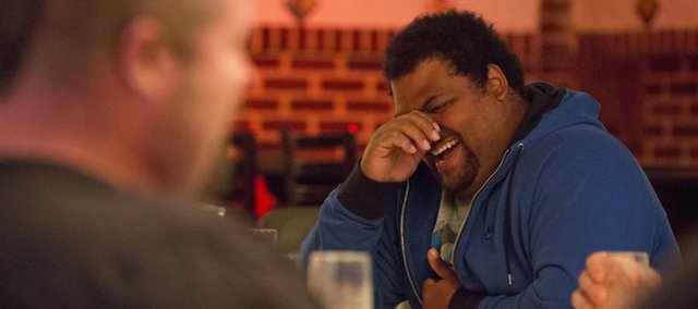 Shot put Olympian Reese Hoffa is unable to hold back a laugh as fellow Olympian Christian Cantwell, foreground, shares a story during a dinner Tuesday, April 16, 2013, at the Eldridge Hotel in downtown Lawrence. The pair will duel it out today in the men's elite pro shot put event at the Kansas Relays. This year's event has been moved from downtown Lawrence to the livestock arena at the Douglas County Fairgrounds because of severe weather concerns.