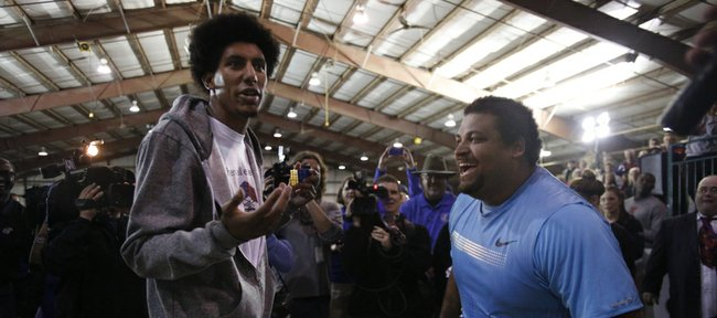 Kansas basketball forward Kevin Young throws up his hands after losing to Reese Hoffa in a Rubik's Cube competition following the Elite Men's Shot Put event of the 2013 Kansas Relays in the livestock arena of the Douglas County Fairg