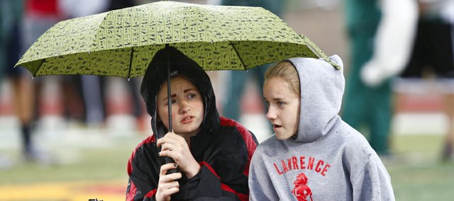 Lawrence High sophomore Kennedy Dold, left, and freshman Kaytlin Riedesel duck under an umbrella as the rain comes down during the start of the Free State Track and Field Invitational on Monday, April 22, 2013 at Free State High School.