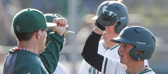 Free State's Cooper Karlin, right, gets elbow bumps from his coaches and teammates after he and teammate Joe Dineen scored on a third-inning dropped ball in the outfield by Olathe South on Wednesday, April 24, 2013 at Free State High School. Nick Krug/Journal-World Photo