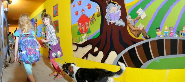 "Pinckney Elementary students Edith Patterson, 7,  and Annabelle Hurst, 9, walk with Patterson's dog Rosie, through the tunnel beneath Sixth Street on their way home from school Tuesday. New mural panels line both walls the length of the tunnel thanks to artists from Van Go Inc. with help from the Pinckney PTO, the city of Lawrence, Lawrence Schools Foundation, and the Old West Lawrence and Pinckney Neighborhood associations. The panel at right includes references to, from left, The Little Red School House, Hugh Cameron aka ""the Kansas Hermit"" and John Brown. A mural unveiling ceremony is scheduled for Friday at 5 p.m."